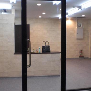外装リフォーム後のガラス張りの店舗入り口