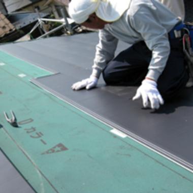 屋根に防水シートを張る作業中
